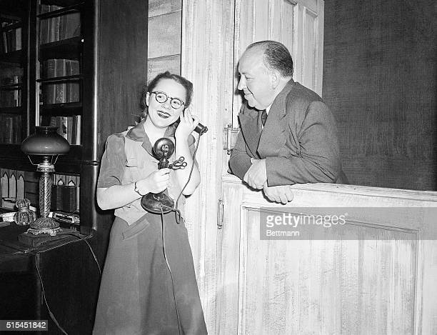 """Boston, MA-Alfred Hitchcock , noted film director, smiles as he watches his daughter Pat answer the phone during rehearsal for """"Violet,"""" in which she..."""