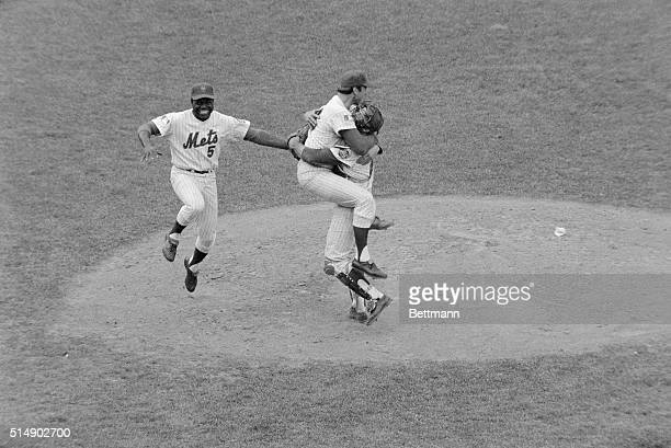 New York, NY: Met third baseman Ed Charles jumps with joy as pitcher Jerry Koosman and catcher Jerry Grote hug each other after the New York Mets...