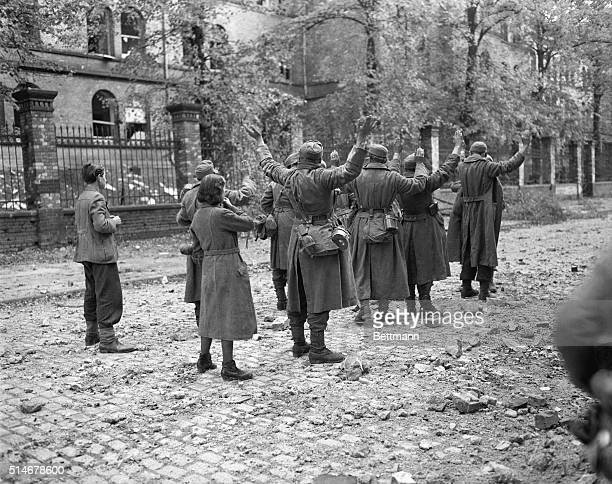 Arms raised high German soldiers give themselves up to advancing American troops in the streets of Aachen Two civilian residents of the Nazi bastion...
