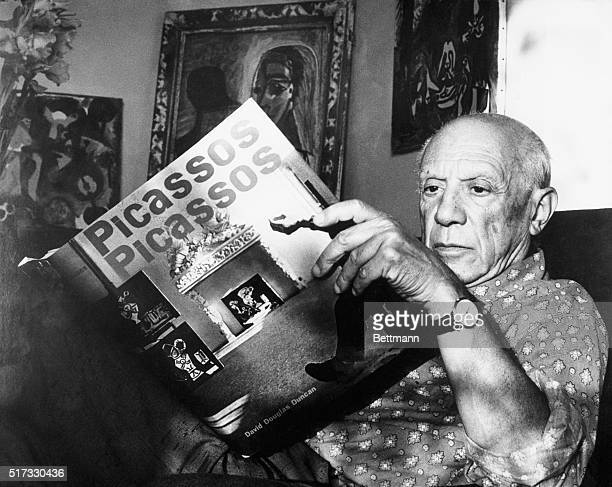 10/19/61Vallauris France Pablo Picasso thumbs through book of 102 photographs in full color which record the cream of the artist's own collection of...