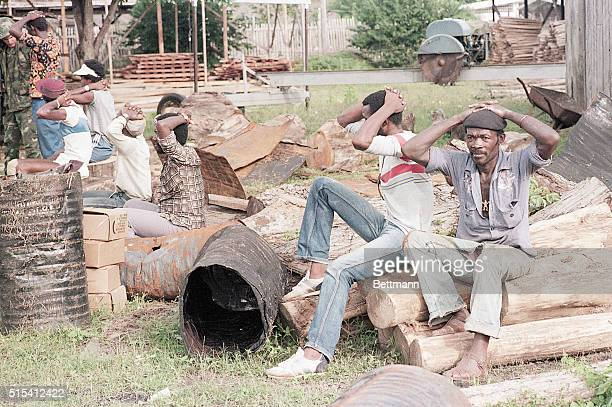 A group of Grenadians seated amidst a pile of rubble with their hands on their head as they are captured during the US invasion of Grenada