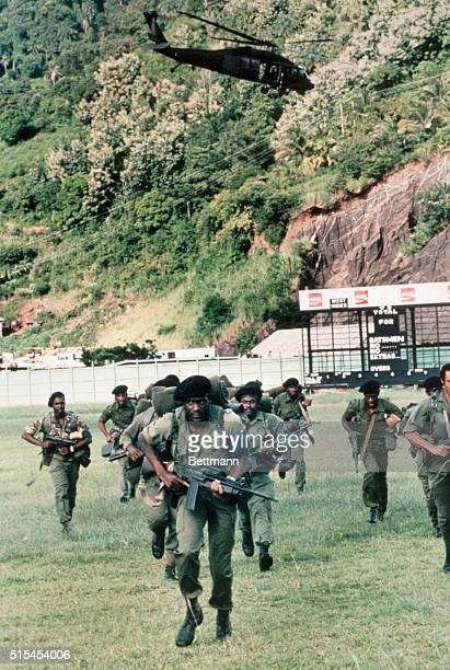 A troop of combatready United States Marines make their way across a sports field during the United States invasion of the island of Grenada
