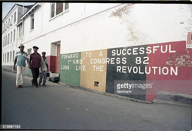 Residents of Grenada walk past a mural that reads Forward to Successful NWO Congress 82 Long Live the Revolution Photographed during the US invasion...