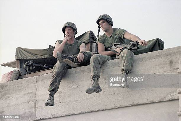 Two US soldiers relax with their guns while seated atop of a barricade during the US invasion of Grenada