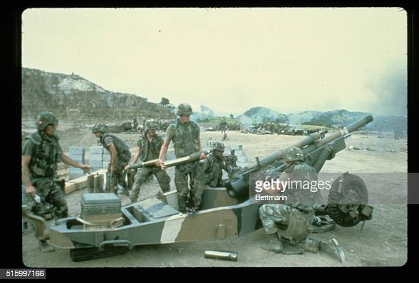 United States soldiers fire a cannon during the United States invasion of the island of Grenada