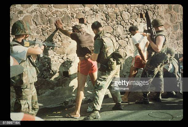 United States soldiers search captives who are being held at gunpoint against a wall during the United States invasion of the island of Grenada