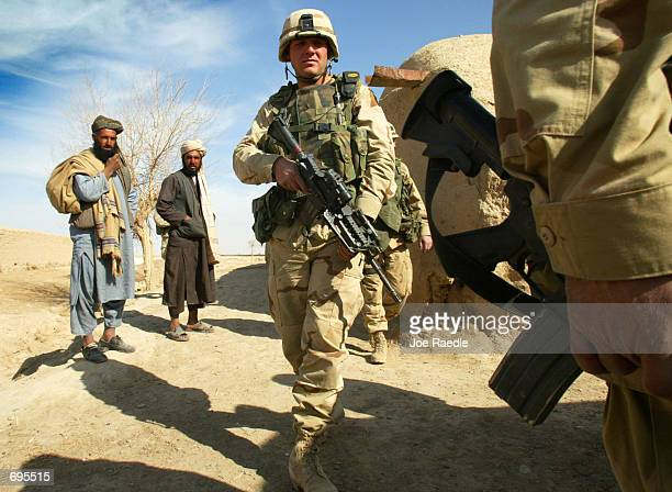 101st Airborne division of the Army Staff Sgt Joshua McFaul from New London Wisconsin walks through an Afghan village February 9 2002 on the...