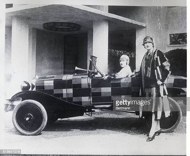 London England Here is pictured one of the new smart automobiles shown at the exposition building in Paris Standing by the car which design is the...