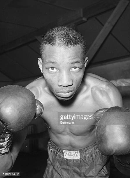 Summit, NJ- Sandy Saddler raises his gloved fists, with which he expects to beat the featherweight champion Willie Pep, when they meet in Madison...