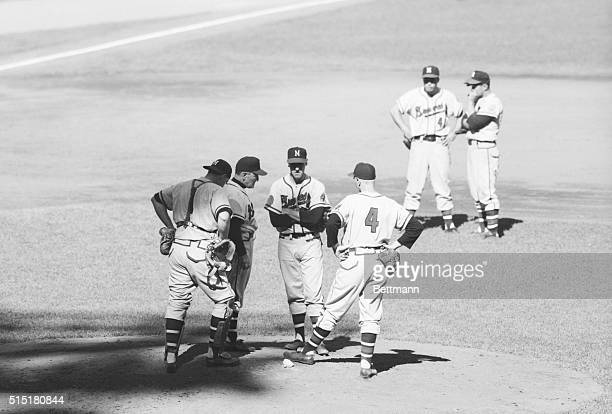 Conference on mound during first game of the 1957 World Series. Left right are: Del Crandall; Fred Haney; and Warren Spain.