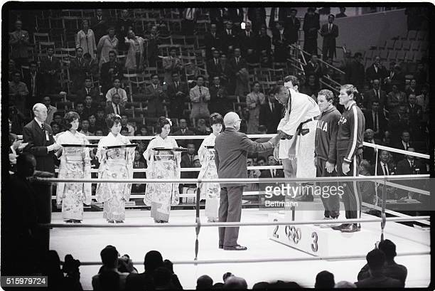 Tokyo Japan Joe Frazier of Philadelphia is shown shaking the hand of the official who has awarded the medals in the ring at an Olympics ceremony in...