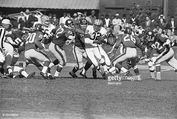Cleveland OH Browns' Jim Brown goes for a first down in the first quarter on a short gain and is chased by Giants' Andy Stynchula John LoVetere and...