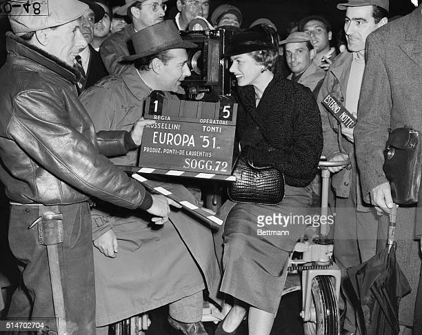 Rome Italy Director Roberto Rosselini leans across a camera lens to deliver lastminute instructions to his beautiful wife Swedish born Ingrid Bergman...