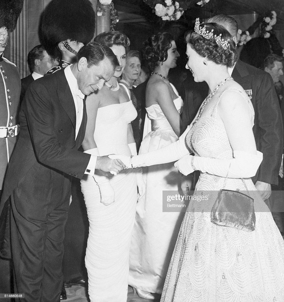 Entertainer Frank Sinatra (left) bows as he is presented to smiling Queen Elizabeth at movie premiere here, Oct. 27. The film being shown was Danny Kaye's 'Me and the Colonel.' Sinatra and Kaye returned to the U.S. 28, on a jet flight.