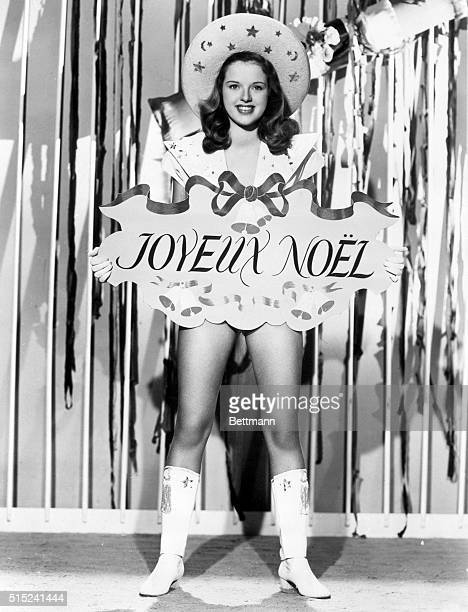 London, England- Diana Dors, British film player, holds an early Christmas greeting in French. The costume doesn't look very wintery.