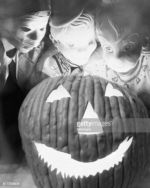 Chicago IL weaving a special Halloween spell by the light of a grinning pumpkin three fiveyearolds goblins do their part to make it a spooky holiday