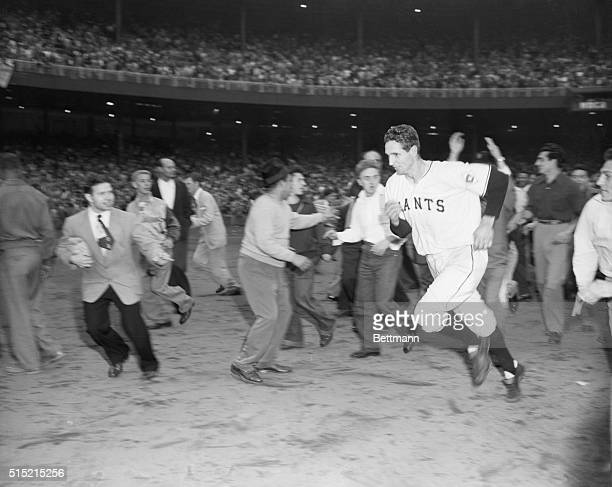 New York, NY- Bobby Thomson, surrounded by excited and worshipping fans, runs for the Giant dressing room after his pennant-winning homer in today's...
