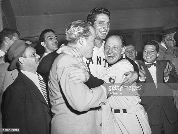 New York, NY- Owner of the Giants, Horace Stoneham, and manager Leo Durocher, hug hero of the game Bobby Thomson following his pennant-winning homer...