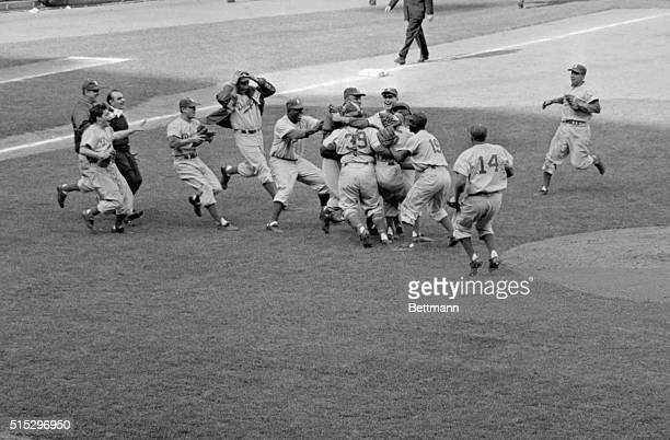 New York, NY: Dodgers rush to the mound to embrace young southpaw Johnny Podres after he hurled the final ball in today's 2-0 victory over the Yanks....