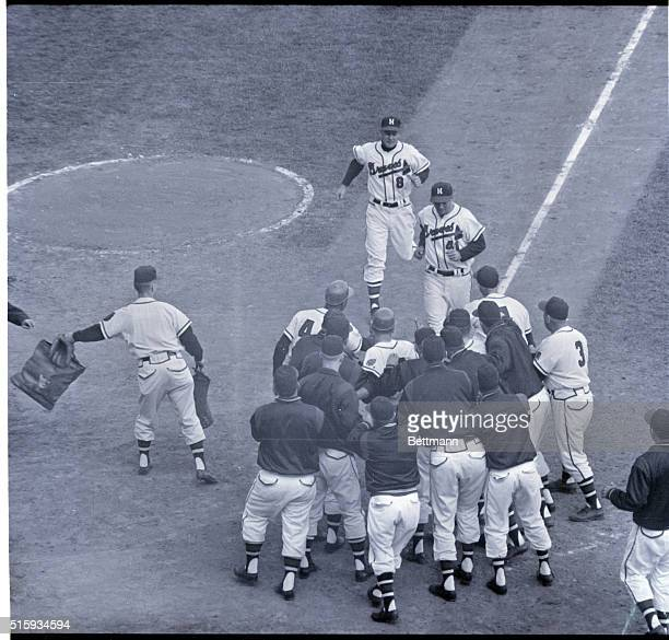 10/6/1957Milwaukee WI County Stadium Eddie Mathews approaches home plate which is loaded with players for the Milwaukee Braves waiting to...