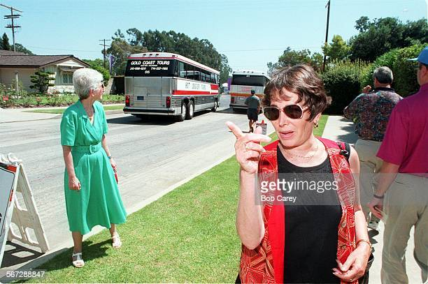 BC/f–––Meri Bender right points at buses carrying fans into PGA Tournament at Riviera Country Club as fellow homeowner Renee Chanon left watches...