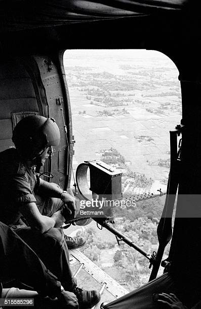 Quang Ngai Province, South Vietnam: An American soldier keeps watch from airborne helicopter carrying Vietnamese troops over marshlands south of...