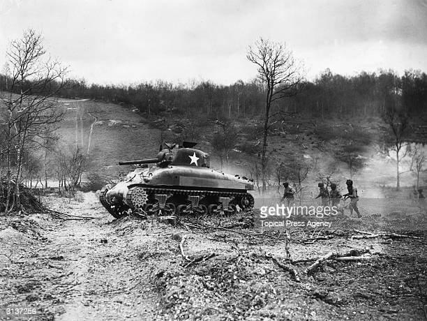 A Sherman tank followed by American Combat Engineer troops in training prior to Dday