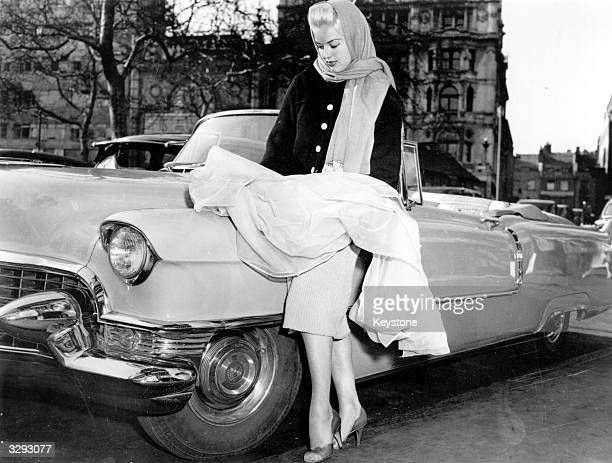 Diana Dors the starlet with the Cadillac in which she arrived at the Cannes Film Festival