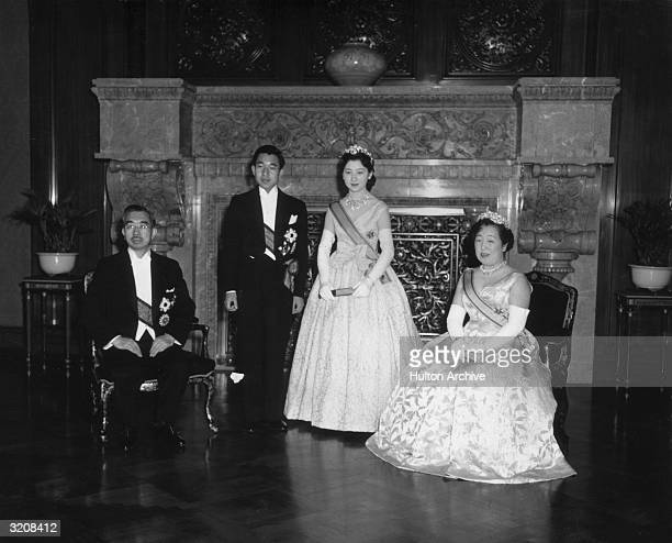 Fulllength portrait of Crown Prince Akihito and Crown Princess Michiko standing between his parents the Emperor Hirohito and the Empress Nagako after...