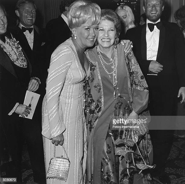 American actors Betty Grable and Martha Raye embrace at the Academy Awards Dorothy Chandler Pavilion LA County Music Center Los Angeles California...