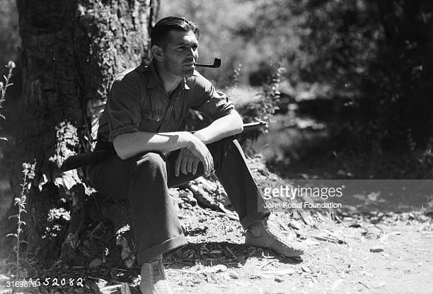 American leading man Clark Gable smoking a pipe at the foot of a tree