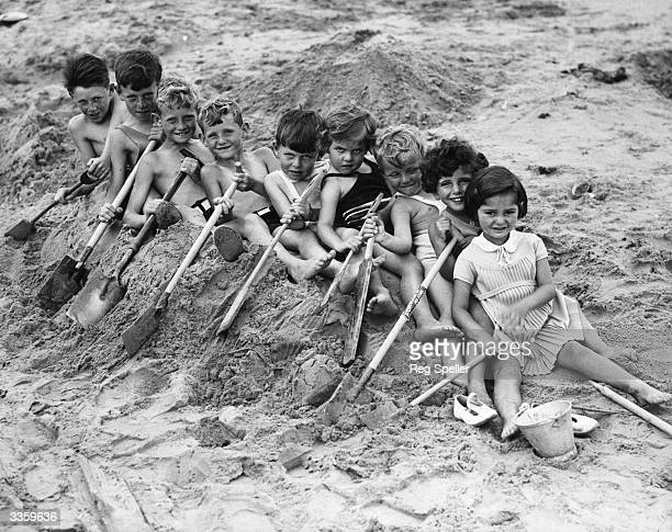 A group of children on the beach at Frinton on Sea in Essex sail away in their sand boat