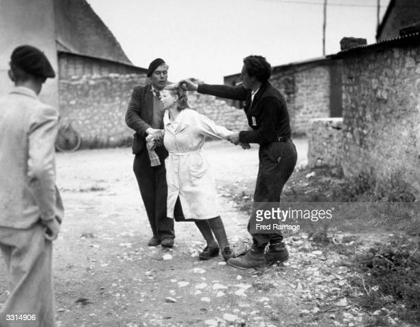 Two French patriots cutting off the hair of a woman who was caught collaborating with the Germans
