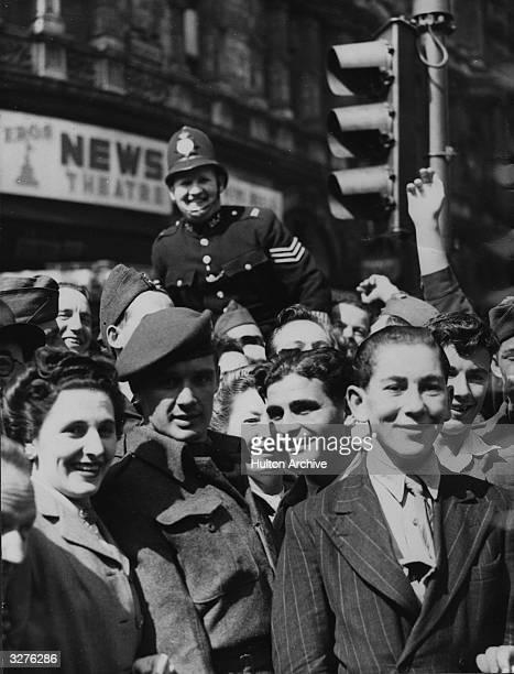London policeman joins the celebratory crowds in London's West End, following the news of Japan's surrender.