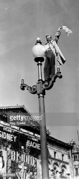 Man waving from a lamppost to the crowds below in Piccadilly Circus, London, during the celebrations following the news of Japan's surrender.
