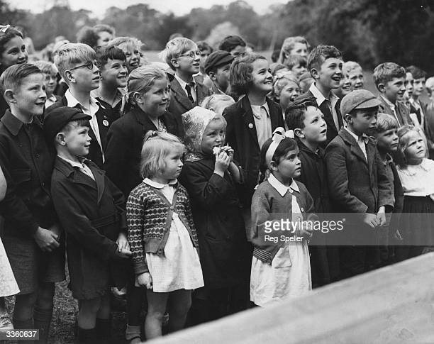 Children watch a Punch and Judy show in a park at Catford London