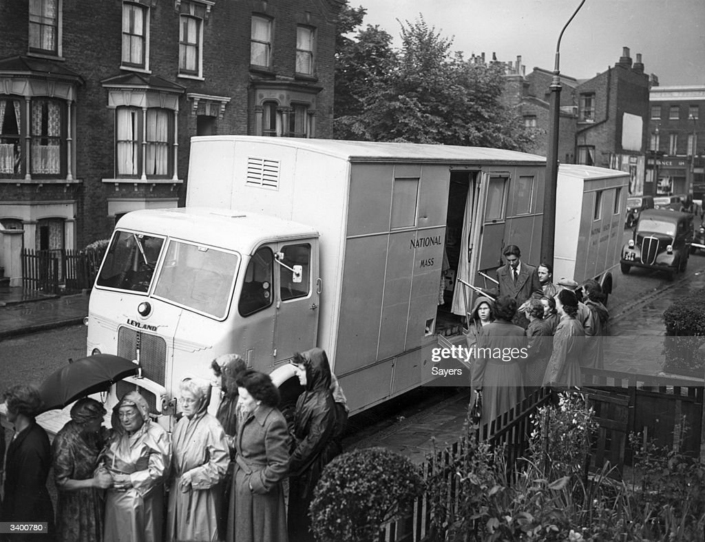 National Health Service patients queuing in the rain outside a mobile X-ray unit parked in a street in New Cross, south-east London. The unit operates from New Cross General Hospital.