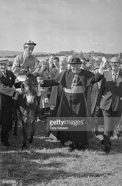 The Bishop of Southwark, the Right Reverend Cyril Cowderoy leads a jockey on a donkey at the Epsom races.