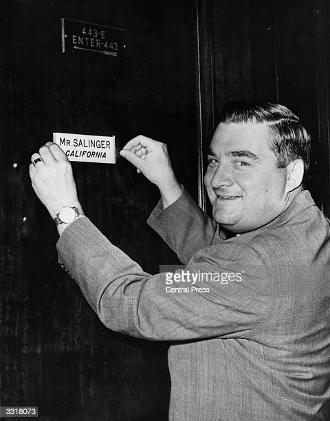 Former White House press secretary, Pierre Salinger, pinning his name on the door of his new office, where he has been appointed States Senator for...