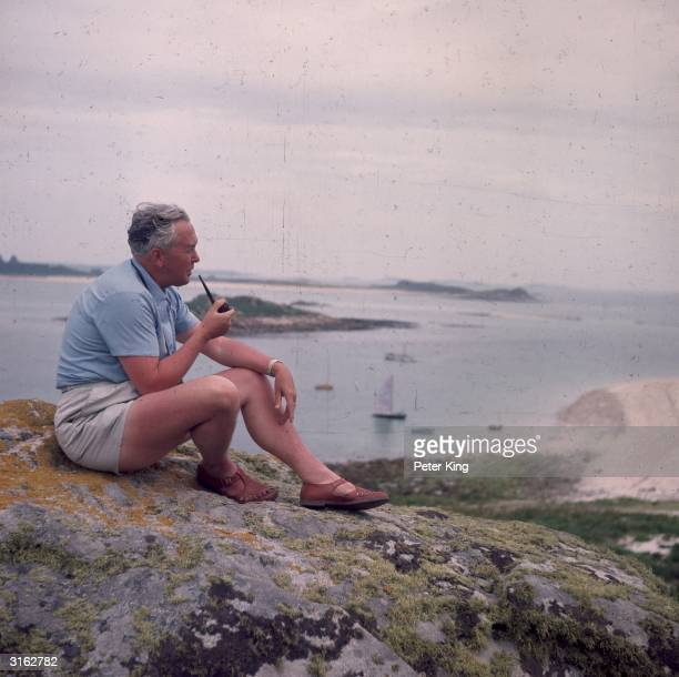 British Labour politician and Prime Minister Harold Wilson sitting quietly smoking his pipe on a rock during his holiday to the Scilly Isles