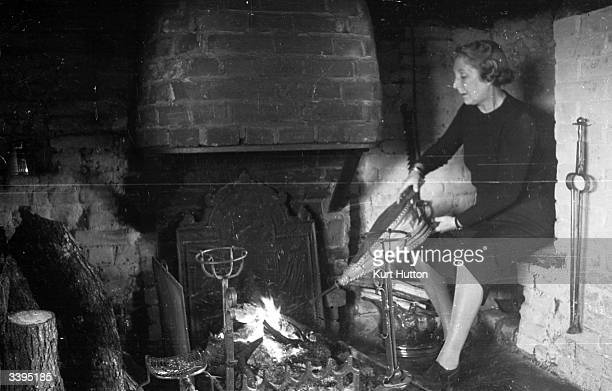 A woman pumps a bellows into the fireplace of 'Punch' cartoonist George Belcher's country cottage in Chiddingford near Guildford in Surrey Original...