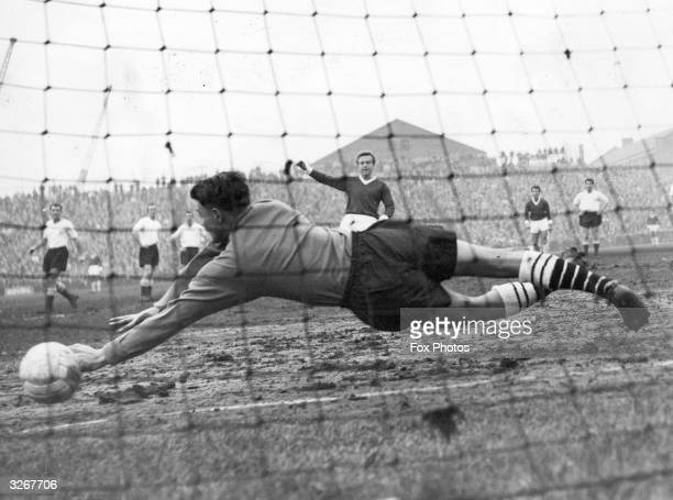 Fulham goalkeeper Hewkins gets his hands to the ball but fails to stop Manchester United's Quixall from scoring during their league match at Craven...