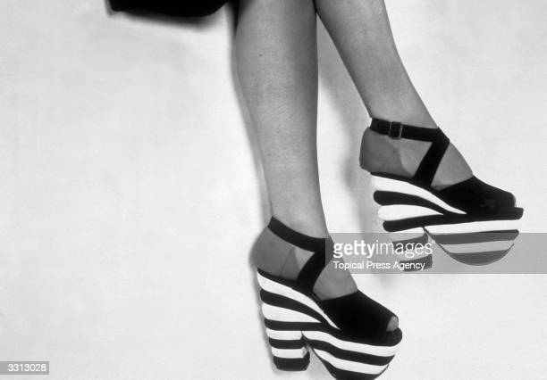 Pair of platform shoes with black and white striped soles.