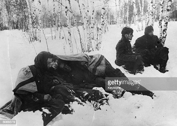 A group of German prisonersofwar huddle under a blanket as their Russian captors push towards Kharkov capital of the Ukraine during World War II