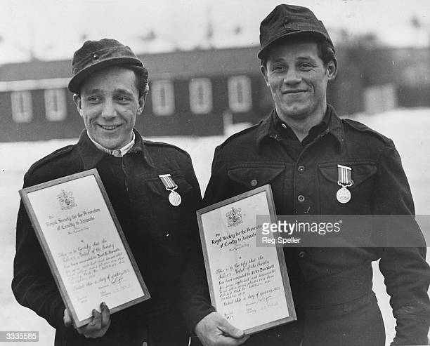 Two German prisoners of war with their medals and certificates awarded by the RSPCA for jumping into icy water to rescue a horse The men have also...