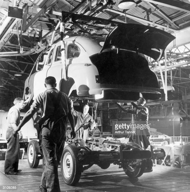 Workers lower the bodywork of a Standard Vanguard car onto its chassis at the company's factory at Coventry