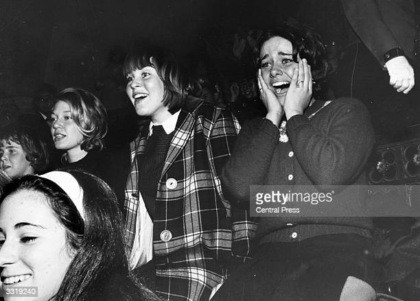 Group of Beatles fans watching their heroes perform on the American television programme 'The Ed Sullivan Show'.