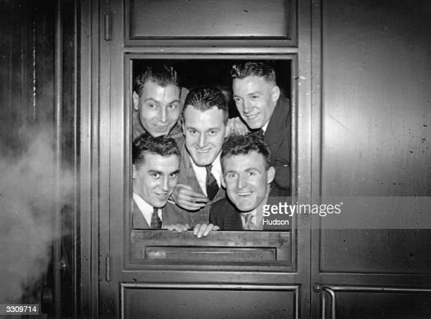 Five of the Chelsea team peering out of the train window as they leave Liverpool Street Station London for Norwich Woodley Bambrick Spence...