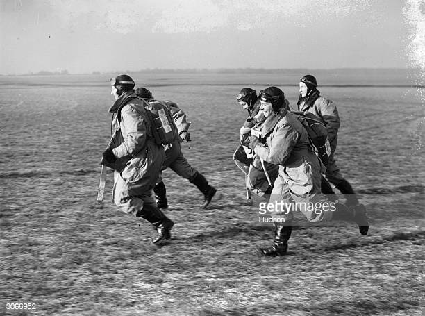 Women pilots of the Transport Auxiliary Service who ferry new RAF aircraft from factory to aerodromes running to their planes to give a demonstration...