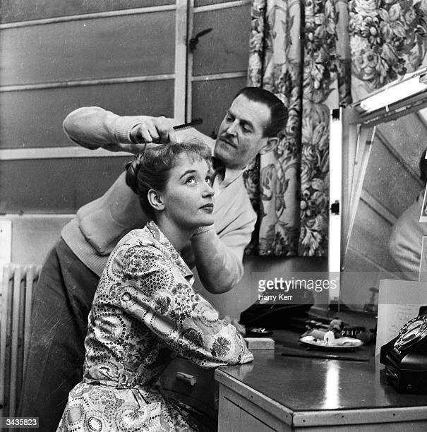 English actress Sylvia Syms is visited by the hairdresser whilst filming 'No Time for Tears' at Elstree Studios Hertfordshire